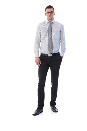 casual business: Confident young businessman standing with hands in pocket, smiling.