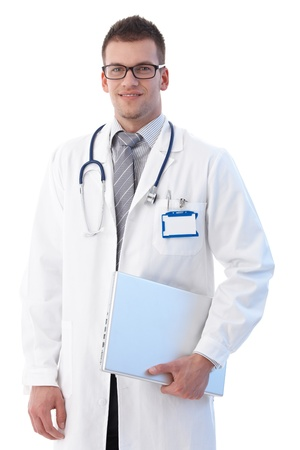 Medical student standing with laptop in hand, smiling. photo