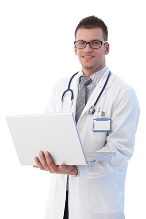 Cheerful young doctor holding laptop in hand, smiling. photo