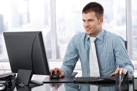 using computer: Young businessman sitting at desk in modern office, working on computer, smiling.