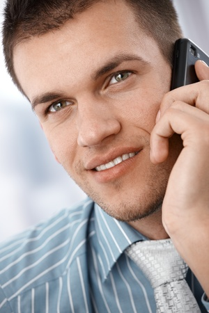 Closeup portrait of young businessman using mobile phone, smiling. photo