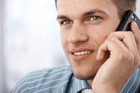 handsome young businessman talking on mobile phone, smiling photo