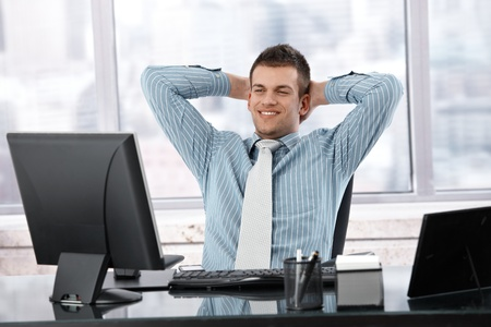 stubbly: Satisfied businessman sitting at desk in bright office, looking at screen.