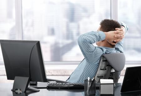 Businessman sitting in Stuhl, ruhen im Amt. Standard-Bild