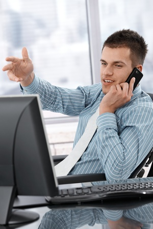 handheld computer: Young manager sitting at desk, using mobile phone, working Stock Photo