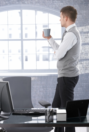 Businessman standing in bright office, looking out of window, drinking tea, thinking. photo