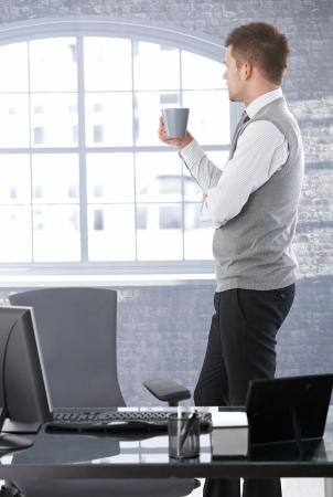 adentro y afuera: Empresario permanente en la Oficina brillante, mirando por la ventana, beber t�, pensando.