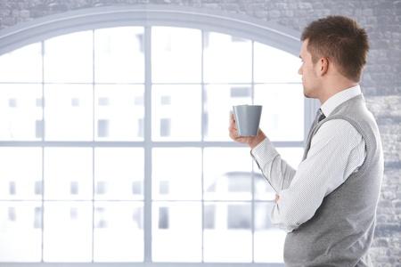 Homme occasionnel regardant par la fenêtre, de penser, de boire du thé.
