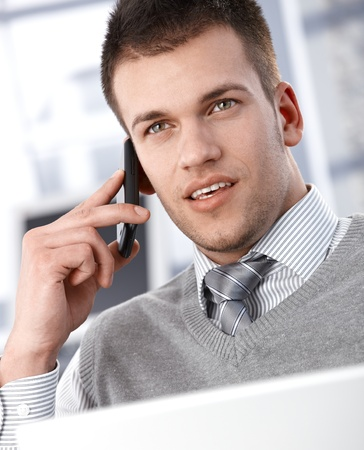 Goodlooking young businessman talking on mobile phone. Stock Photo - 9538212