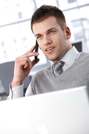 Young businessman talking on mobile phone, sitting in bright office. Stock Photo - 9538217