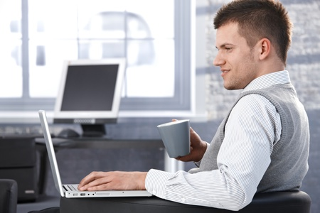 browse: Young businessman working in office, using laptop, sitting in armchair.