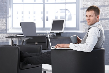 Young businessman sitting in office, resting legs in armchair, using laptop, smiling at camera. Stock Photo - 9538213