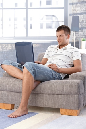 Handsome young man using laptop at home, sitting in armchair, smiling. photo