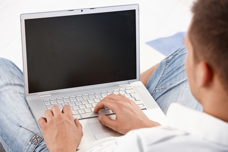 Young man holding laptop in lap, working on it, photographed from behind. Stock Photo - 9538231