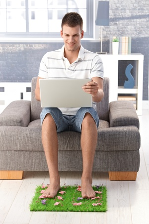 College student sitting in armchair in living room, using laptop, resting legs on artificial grass, smiling. photo