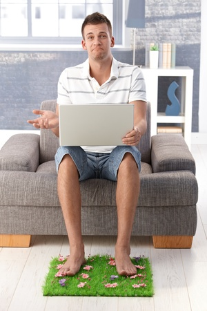 Disappointed young man sitting in armchair at home with mouth curving down, using laptop, resting legs on artificial grass. Stock Photo - 9538333