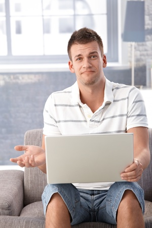 Unhappy man sitting in armchair at home, looking disappointed. Stock Photo - 9538179