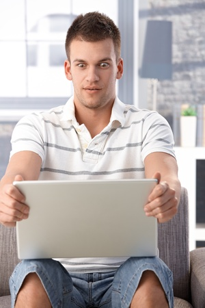 Young man sitting at home using laptop, staring at screen shocked. Stock Photo - 9538238