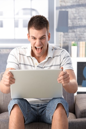 Young man sitting at home in armchair, using laptop, shouting at laptop screen. photo