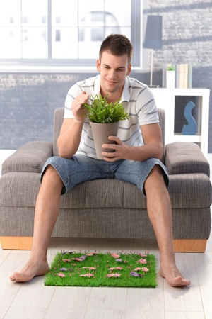 buen vivir: Joven sentado en su casa en el sill�n, con planta en la mano, con c�sped artificial, anhelo de naturaleza, sonriendo. Foto de archivo