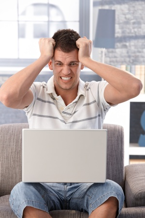 College student sitting in armchair at home, looking at laptop screen shocked. Stock Photo - 9538232