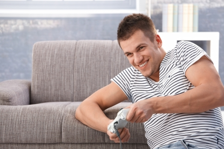 controller: College student playing video game at home in living room, having fun, smiling.