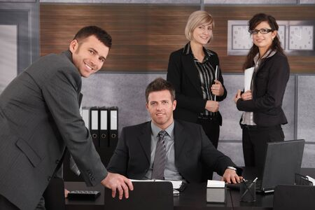 Business executive sitting in office, looking at camera with team standing around. photo