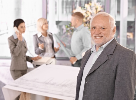 Smiling senior businessman and team working in bright office. photo