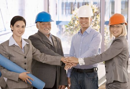 Team portrait of happy architects standing in office, holding hands together expressing teamwork and unity. Stock Photo - 9538297