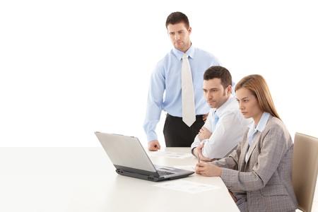 trabajador oficina: J�venes colegas sentados a la mesa, utilizando equipos port�tiles, teamworking.