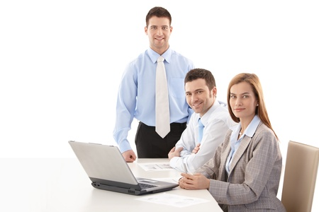 co work: Happy, young businesspeople sitting at table, working together, smiling.