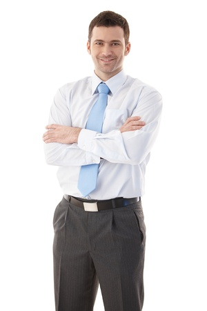 happily: Confident businessman standing arms crossed, smiling happily. Stock Photo