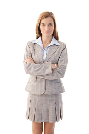 skirt suit: Confident young businesswoman standing arms crossed, wearing mini skirt. Stock Photo