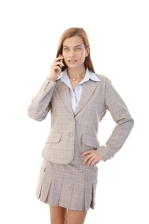 Young attractive businesswoman using mobile phone, standing over white. photo