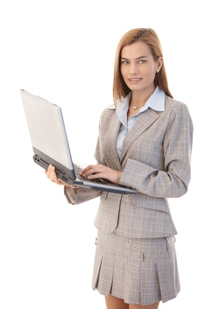 mini jupe: Attractive female casual office worker using laptop, smiling.