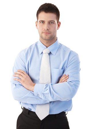 severity: Confident young businessman standing arms crossed over white background.