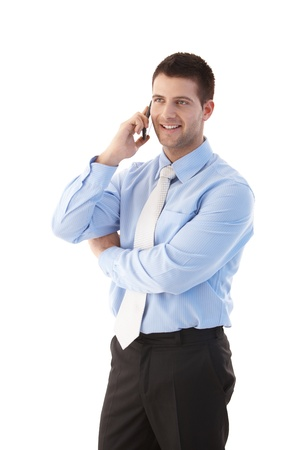 talking businessman: Cheerful young businessman talking on mobile phone, smiling.