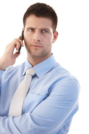 Troubled young businessman talking on mobile phone. Stock Photo - 9538149