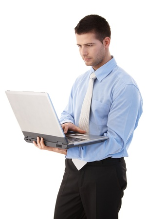 Young casual office worker holding laptop in hand, looking at screen, working. photo