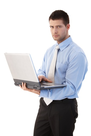 Goodlooking young businessman working on laptop, standing over white background. photo