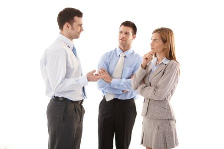 Young businesspeople standing over white background, talking, smiling.