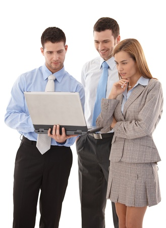 Young businesspeople browsing internet on laptop, smiling. photo