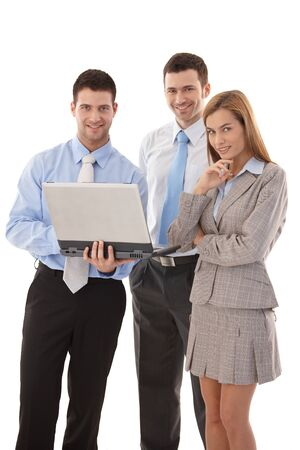 Happy team of young businesspeople working together on laptop, smiling. photo