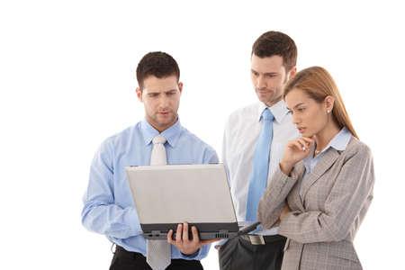 computer problems: Giovani imprenditori di lavoro sul computer portatile, in piedi, guardando turbata.