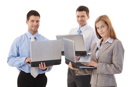 Young confident businesspeople standing with laptops in hands, working, smiling. photo