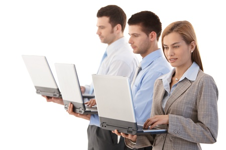Young, attractive businesspeople using laptops, working individually. photo