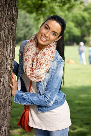 Happy young woman having fun in park, smiling, looking at camera. Stock Photo - 9562309
