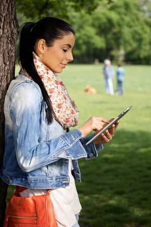 Young female using tablet, standing by tree in park, side view. photo