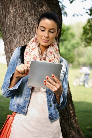 Casual young woman using tablet PC in park. Stock Photo - 9562286