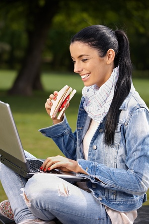 Happy young woman browsing internet in park, having lunch, smiling. photo